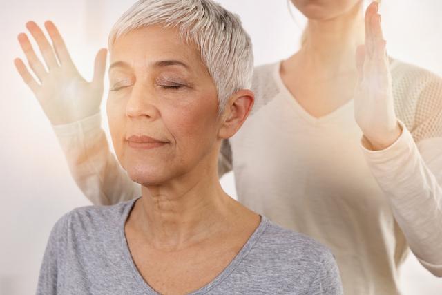 eine heilerin hält ihre hände über den kopf einer frau