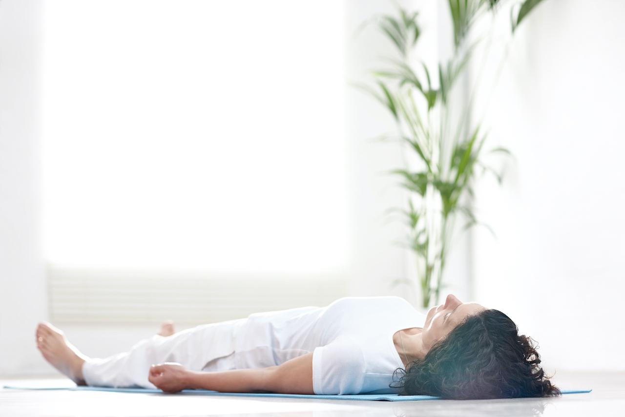 eine frau liegt auf der yogamatte